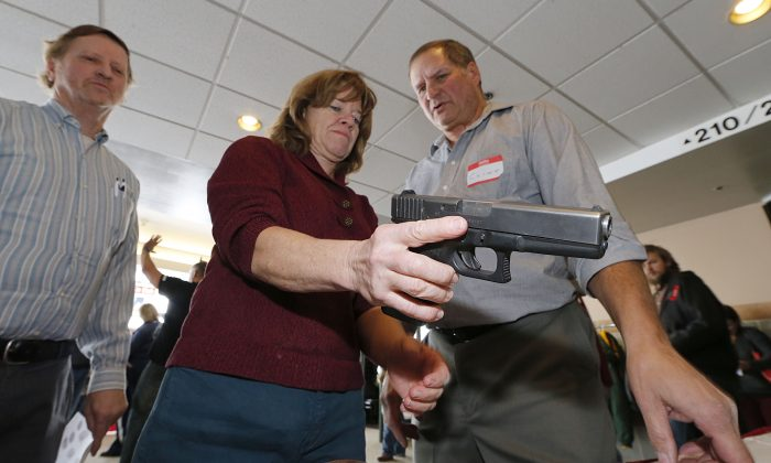 A Utah teacher is shown how to handle a handgun by instructor Clint Simon (R), at a concealed-weapons training class to 200 Utah teachers in West Valley City, Utah on Dec. 27, 2012. (Photo by George Frey/Getty Images)