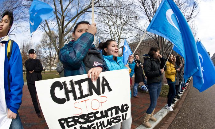 Uyghur activists protest against the visit of Chinese regime head Hu Jintao outside of the White House in Washington, DC, on Jan. 19, 2011. A new report says that Uyghurs across the world, including many in the United States, are being spied on by China's intelligence services. (Nicholas Kamm/AFP/Getty Images)