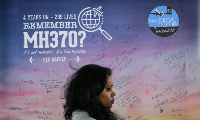 A woman walks past a banner bearing solidarity messages for passengers of the missing Malaysia Airlines flight MH370,  during a memorial event in Kuala Lumpur on March 3, 2018 ahead of the fourth anniversary of at the ill-fated planes disappearance. (Manan Vatsyayana/AFP/Getty Images)