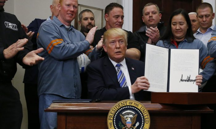 U.S. President Donald Trump holds up a proclamation during a White House ceremony to establish tariffs on imports of steeland aluminum at the White House in Washington on March 8, 2018. (Reuters/Leah Millis)