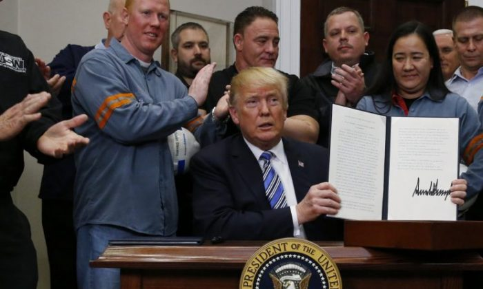U.S. President Donald Trump holds up a proclamation during a White House ceremony to establish tariffs on imports of steel and aluminum at the White House in Washington, March 8, 2018. (Leah Millis/Reuters)