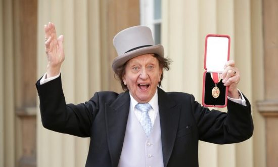 Entertainer Ken Dodd poses for photographers after being made a Knight Bachelor of the British Empire by Britain's Prince William at an investiture at Buckingham Palace in central London, March 2, 2017. (Reuters/Yui Mok/Pool/File Photo)