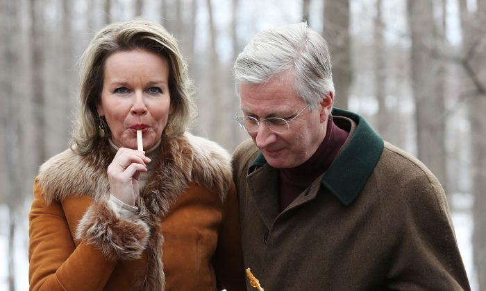 King Philippe and Queen Mathilde of Belgium try freshly made maple taffy during a visit to Richelieu Park Sugar Shack in Ottawa on March 12, 2018.  (Lars Hagberg/AFP/Getty Images)