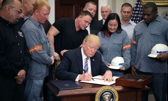 Surrounded by steel and aluminum workers, U.S. President Donald Trump signs a 'Section 232 Proclamation' on steel imports during a ceremony in Roosevelt Room at the White House in Washington, on March 8, 2018. (Chip Somodevilla/Getty Images)