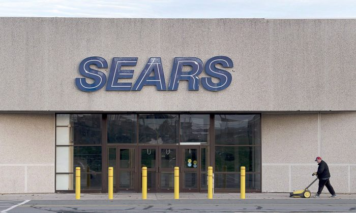 A worker cleans the sidewalk outside a closed Sears store in Dartmouth, N.S. on Oct. 11, 2017. A retail expert said anchor tenants for malls, like Sears, are likely a thing of the past. (The Canadian Press/Andrew Vaughan)
