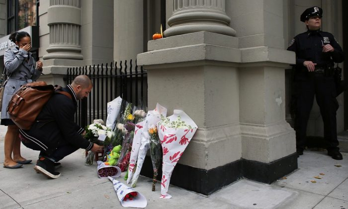 A couple leaves flowers in front of the building where two children were stabbed to death allegedly by their nanny in the family's quiet Upper West Side apartment in New York City on Oct. 26, 2012. (Photo by Spencer Platt/Getty Images)