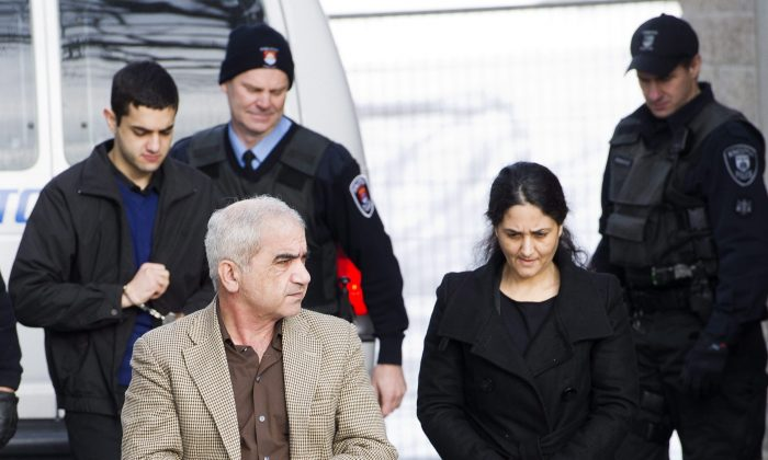 File photo shows Mohammad Shafia, front left,ToobaYahya, front right, and their son Hamed Shafia, back left, being escorted at the Frontenac County courthouse in Kingston, Ontario, on Jan. 28, 2012. (The Canadian Press/Nathan Denette)
