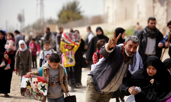 A man gestures as they flee the rebel-held town of Hammouriyeh, in the village of Beit Sawa, eastern Ghouta, Syria March 15, 2018. (Reuters/Omar Sanadiki)