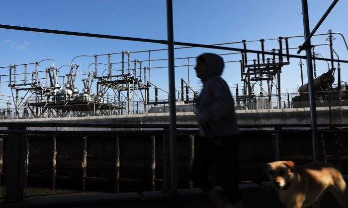 A woman walks by a Con Edison power plant in a Brooklyn neighborhood across from Manhattan on March 15, 2018 in New York City.  (Spencer Platt/Getty Images)