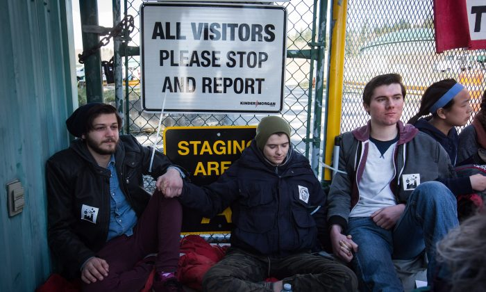 Protesters block a gate outside Kinder Morgan before RCMP officers moved in and arrested them for defying a court order, in Burnaby, B.C., on March 17, 2018. (The Canadian Press/Darryl Dyck)