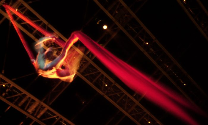 An aerial artist  hangs in a column of red silk during a  rehearsal of Cirque du Soleil show in Boston, Massachusetts,on July 24, 2002. (William B. Plowman/Getty Images)