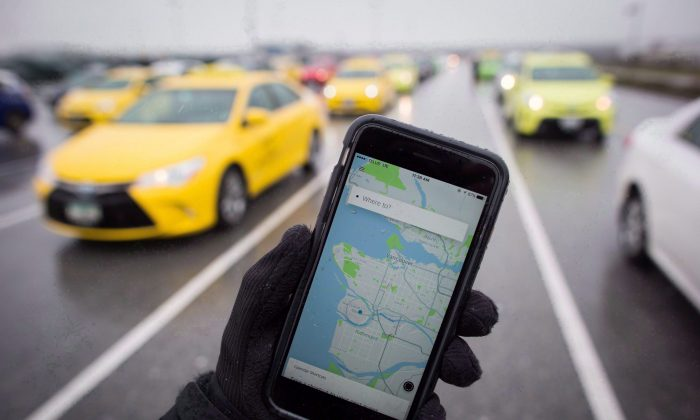 The Uber app is displayed on an iPhone while in the background taxi drivers wait for passengers at the Vancouver International Airport on March 7, 2017. (The Canadian Press/Darryl Dyck)