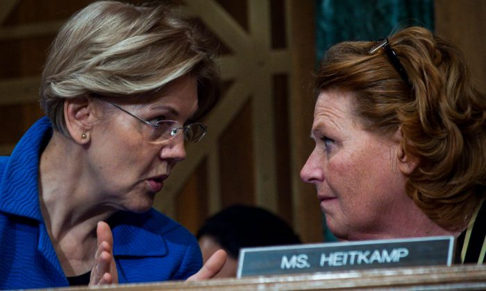 Senators Elizabeth Warren (D-Mass.) and Heidi Heitkamp (D-N.D.) confer during a Senate hearing in Washington on Jan. 30. Heitkamp accused Warren of exaggerating the danger posed by the changes to the Dodd-Frank Act. (Pete Marovich/Getty Images)