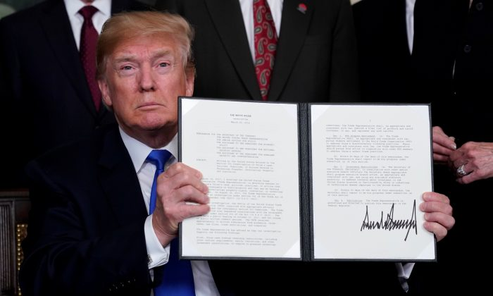 U.S. President Donald Trump holds his signed memorandum on intellectual property tariffs on high-tech goods from China, at the White House in Washington, U.S. on March 22, 2018. (Jonathan Ernst/Reuters)