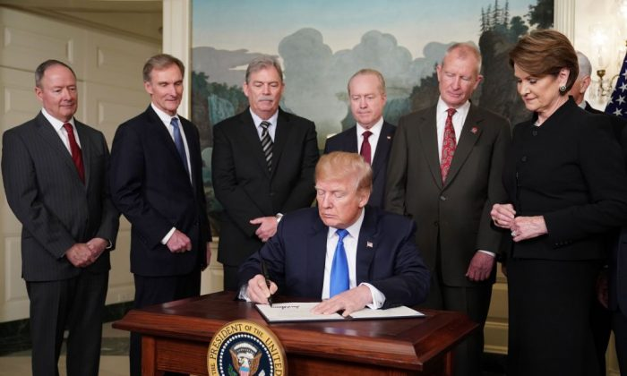 President Donald Trump signs trade sanctions against China in the Diplomatic Reception Room of the White House in Washington, DC, on March 22, 2018.