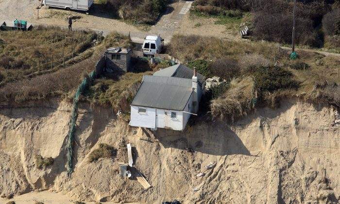 A home in Hemsby, Norfolk, UK, hangs over a cliff edge on March 21, 2018, after storms in the last few weeks. (Mike Page via SWNS)