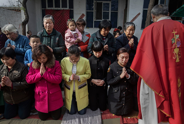 "Chinese Catholic worshippers wait to take communion at the Palm Sunday Mass during the Easter Holy Week at an ""underground"" or ""unofficial"" church near Shijiazhuang, Hebei Province, China, on April 9, 2017. (Kevin Frayer/Getty Images)"