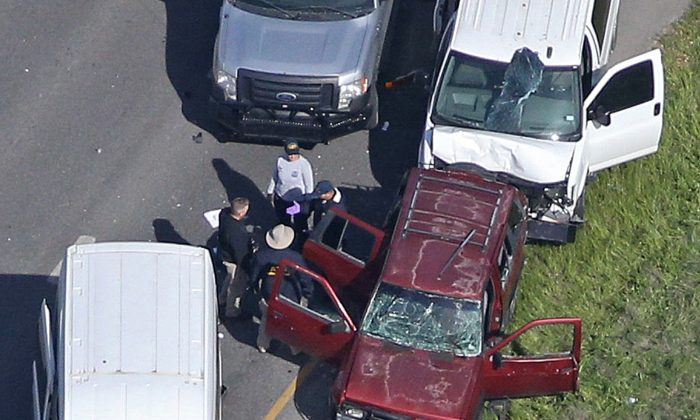 Law enforcement personnel investigate the scene where the Texas bombing suspect blew himself up on the side of a highway north of Austin in Round Rock, Texas. (Reuters/Loren Elliott)