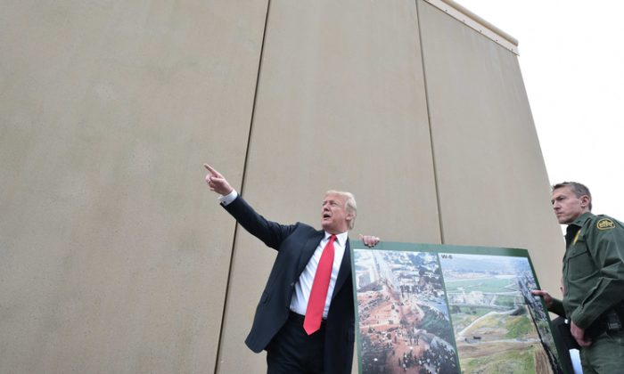 President Donald Trump holds up a poster of before and after photos of a segment of the border wall prototypes with Chief Patrol Agent Rodney S. Scott (R) in San Diego, Calif. on March 13, 2018. (MANDEL NGAN/AFP/Getty Images)