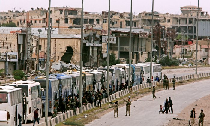 Syrian forces of President Bashar al Assad are seen around buses carry civilian and rebels outside Harasta in eastern Ghouta in Damascus, Syria March 23, 2018. (Reuters/ Omar Sanadiki)