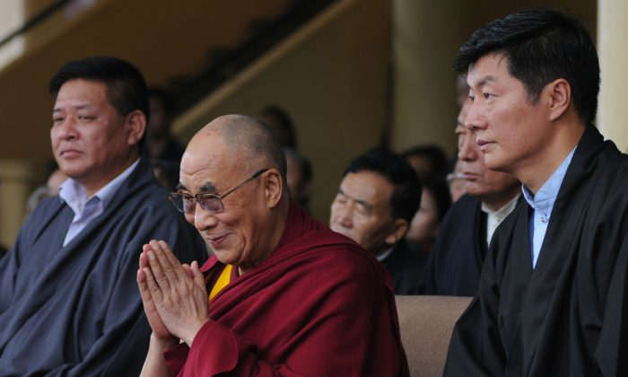 Tibetan spiritual leader the Dalai Lama (C), flanked by President of the Central Tibetan Administration Lobsang Sangay (R) and Speaker of the Tibetan Parliament-in-exile Penpa Tsering (L), greets the audience during the 52nd anniversary of Tibetan Democracy Day at the Tsuglakhang Temple in McLeod Ganj, Dharamsala on Sept. 2, 2012. (STRDEL/AFP/GettyImages)