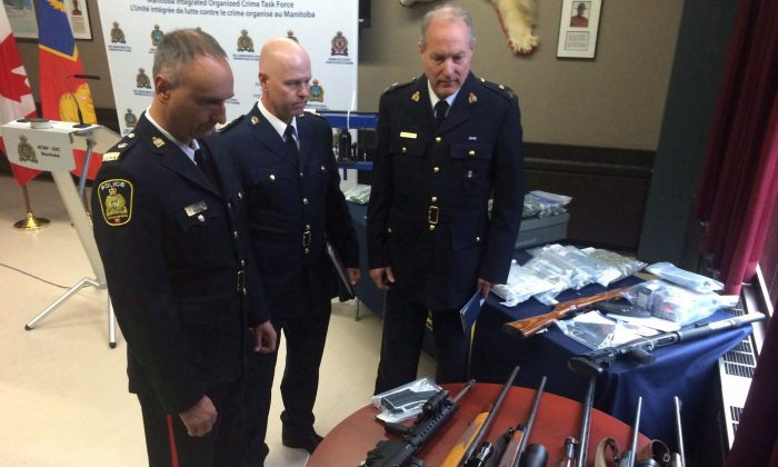 Police display guns, drugs, and other items that were seized during an investigation into the Manitoba drug trade, in Winnipeg on Oct. 19, 2016. Criminals are using the darknet to sell illicit guns to Canadians, the RCMP warns. (The Canadian Press/Steve Lambert)