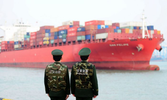 Chinese police officers watch a cargo ship at a port in Qingdao in China's eastern Shandong province on March 8, 2018. (AFP/Getty Images)