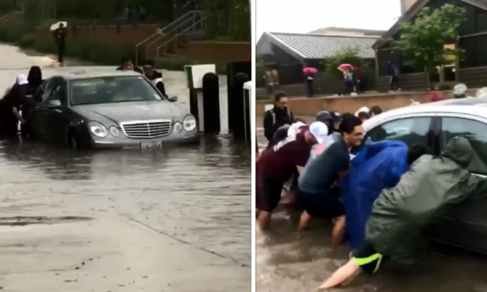 Students Push Car Out of Flooded Street at Texas A&M Campus