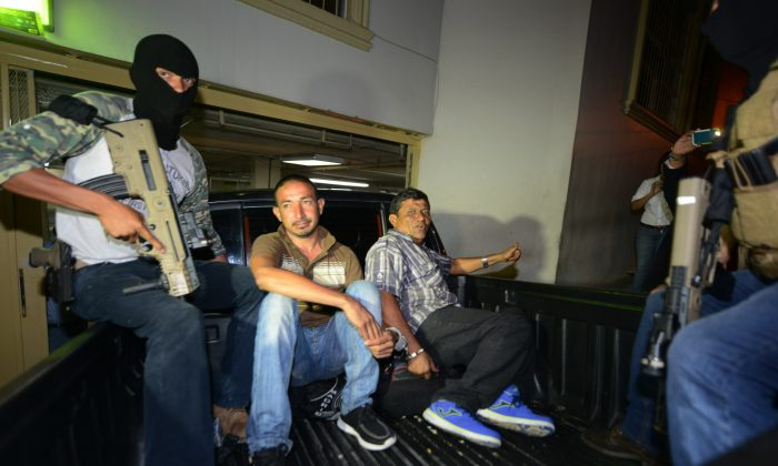 Police take two presumed members of a gang trafficking people to the United States to court in Tegucigalpa, Honduras on June 9, 2016. (ORLANDO SIERRA/AFP/Getty Images)