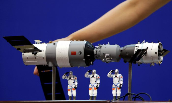 A model of the Tiangong-1 space lab module (L), the Shenzhou-9 manned spacecraft (R) and three Chinese astronauts is displayed during a news conference at Jiuquan Satellite Launch Center, in Gansu province, China June 15, 2012. (Reuters/Jason Lee/File Photo)
