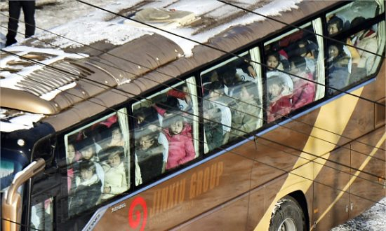 North Korean workers board a bus at customs in Dandong, China's border city with North Korea, on Jan. 9, 2018.  (Kyodo News via Getty Images)