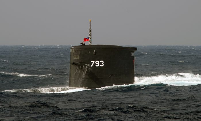 A Taiwanese navy soldier salutes from the Dutch-made Chien Lung-class submarine during a combat skills demonstration in the waters near the Tsoying navy base in southern Kaohsiung, Taiwan on Jan. 14, 2014. (Sam Yeh/AFP/Getty Images)