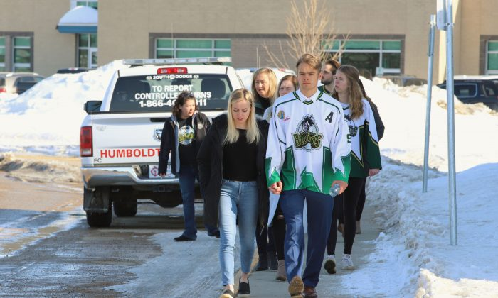 People, including a young man wearing a Humboldt Broncos jersey, approach the Uniplex on April 8, 2018 in Humboldt, Canada, prior to a memorial vigil for the Humboldt Broncos ice hockey team. (Kymber Rae/AFP/Getty Images)