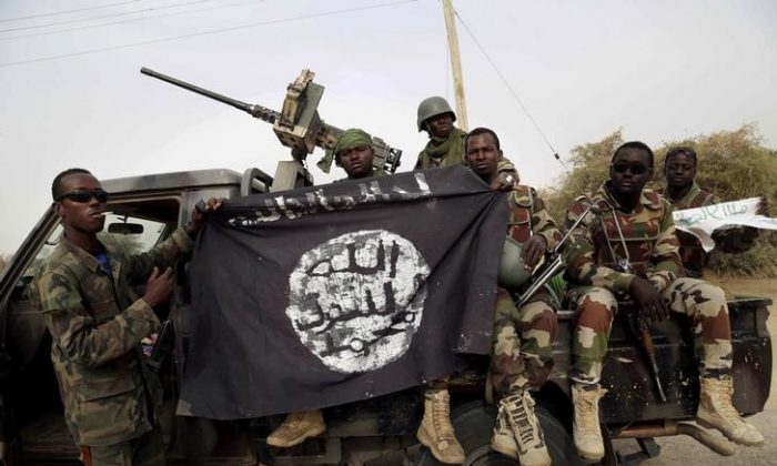 Nigerian soldiers hold up a Boko Haram flag that they had seized in the recently retaken town of Damasak, Nigeria, Mar. 18, 2015. (REUTERS/Emmanuel Braun/File Photo)