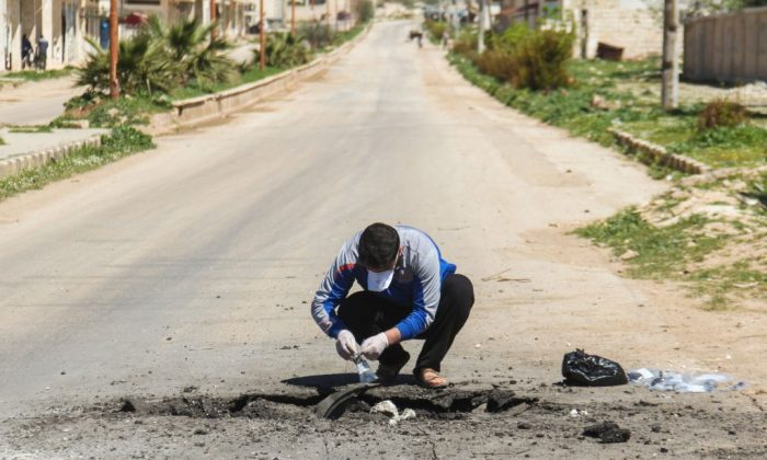A Syrian man collects samples from the site of a suspected toxic gas attack in Khan Sheikhun, in Syrias northwestern Idlib province, on April 5, 2017. (Omar Haj Kadour/AFP/Getty Images)