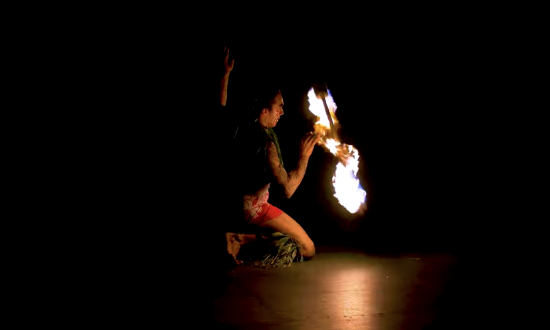 Man is doing a fire knife dance—shows us just exactly what we shouldn't try at home