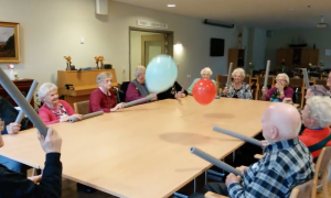 Elderly people are seated around a table, but when the balloons are unleashed—It's game on