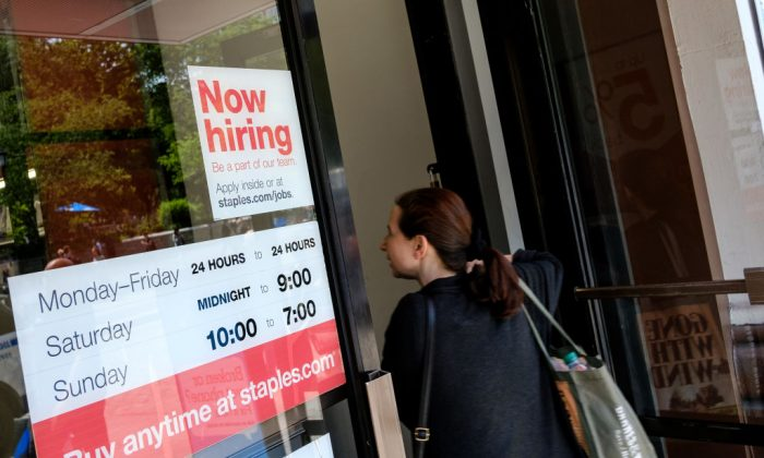 A 'now hiring' sign is displayed on the front entrance to a Staples store in New York City, June 2, 2017. (Drew Angerer/Getty Images)
