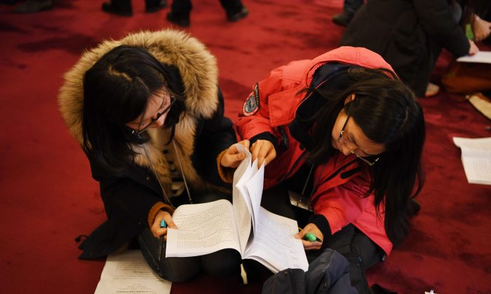 Chinese journalists pore over a copy of the government work report before the opening session of the National People's Congress, the Chinese regime's rubber-stamp legislature, in Beijing on March 5, 2018. (Greg Baker/AFP/Getty Images)