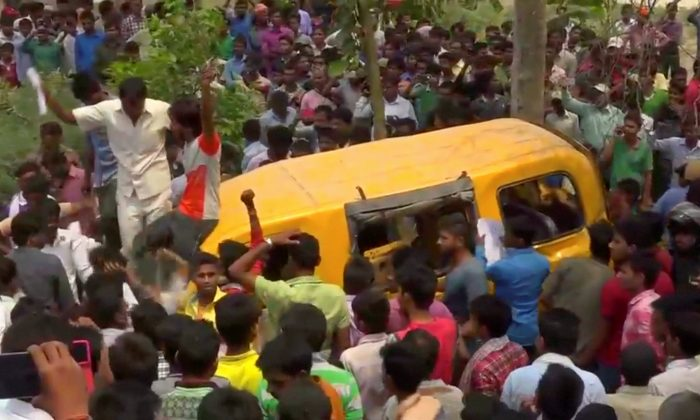People gather around a school bus after it collided with a train in Uttar Pradesh, India April 26, 2018, in this screen grab taken from video. (ANI via Reuters)