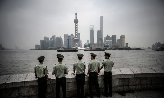 Paramilitary policemen stand in front of the skyline of the Lujiazui Financial District in Pudong in smog in Shanghai on Sept. 29, 2014. (JOHANNES EISELE/AFP/Getty Images)