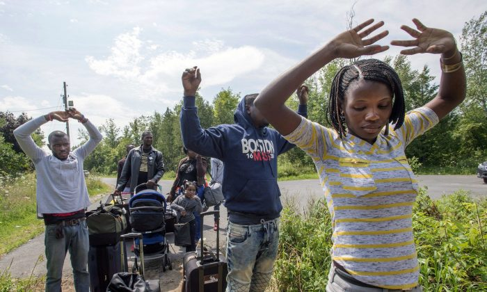 A group of asylum seekers raise their hands as they approach RCMP officers while crossing the Canadian border between Champlain, New York, and St. Bernard de Lacolle, Quebec, on Aug. 4, 2017. (The Canadian Press/Ryan Remiorz)