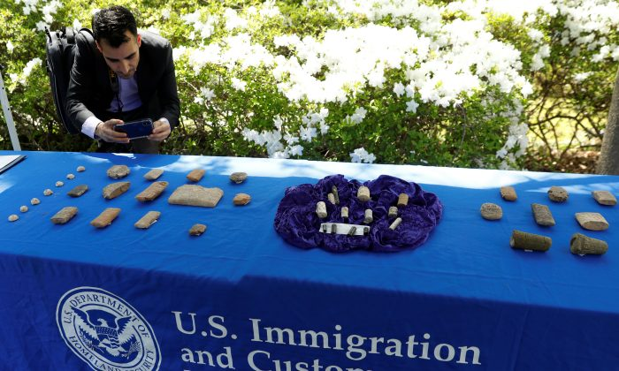 A man photographs artifacts on display, as U.S. Immigration and Customs Enforcement (ICE) hosts an event to return several thousand ancient artifacts to the Republic of Iraq, at the Iraqi ambassador's residence in Washington, DC on May 2, 2018.  (REUTERS/Kevin Lamarque)