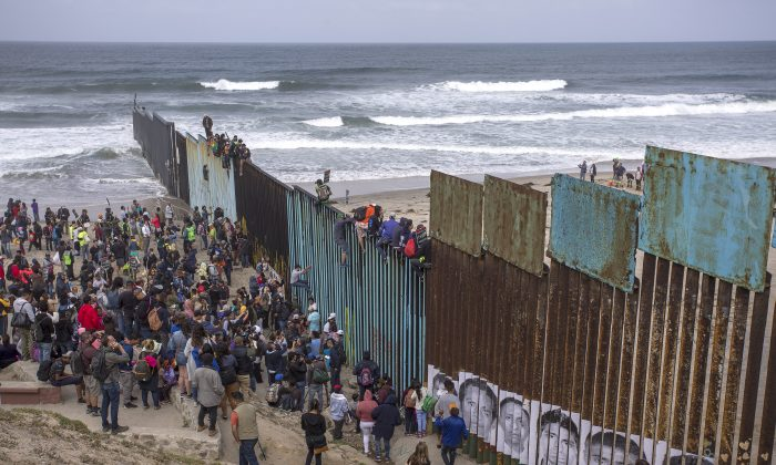 People climb a section of border fence to look into the United States as a caravan of Central American asylum-seekers arrive at the border in Tijuana, Mexico, on April 29, 2018. (David McNew/Getty Images)