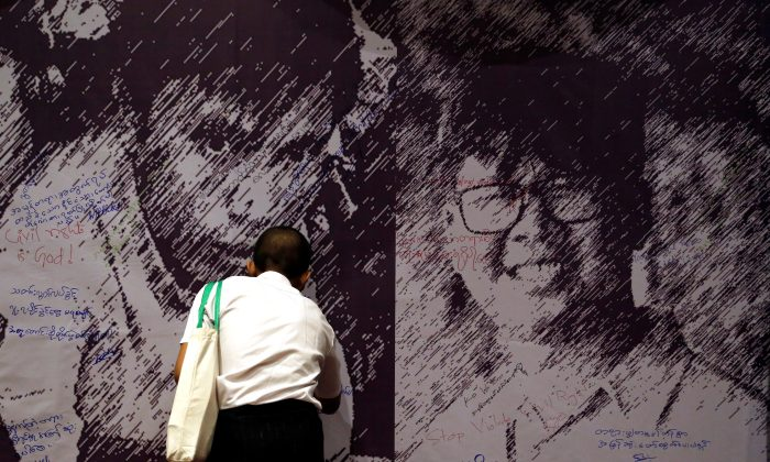 A man writes a goodwill message on a poster depicting detained Reuters reporters Wa Lone and Kyaw Soe Oo at an event discussing press freedom, in Yangon, Myanmar, May 1, 2018. (Reuters/Ann Wang)