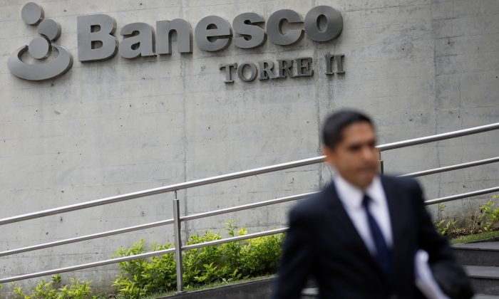 A man walks past the corporate logo of Banesco bank at one of their office complexes in Caracas, Venezuela May 3, 2018. (REUTERS/Carlos Garcia Rawlins)