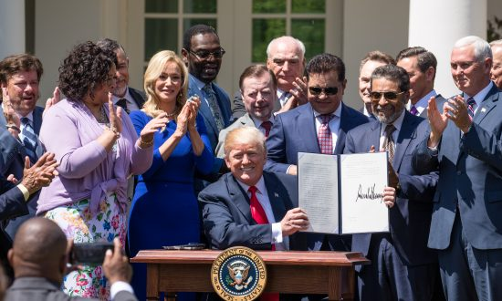 "President Donald Trump signs an Executive Order entitled ""Establishment of a White House Faith and Opportunity Initiative"" at the National Day of Prayer in the Rose Garden of the White House in Washington on May 3, 2018. (Samira Bouaou/The Epoch Times)"