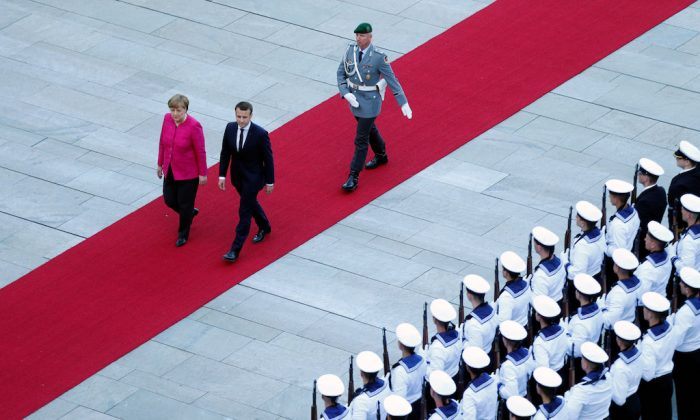 German Chancellor Angela Merkel and French President Emmanuel Macron arrive at a ceremony at the Chancellery in Berlin, Germany, May 15, 2017.    (REUTERS/Hannibal Hanschke)