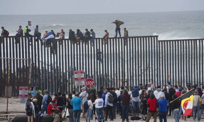 Migrant caravan demonstrators climb the U.S.-Mexico border fence during a rally in San Ysidro, California on April 29, 2018. (Sandy Huffaker/AFP/Getty Images)