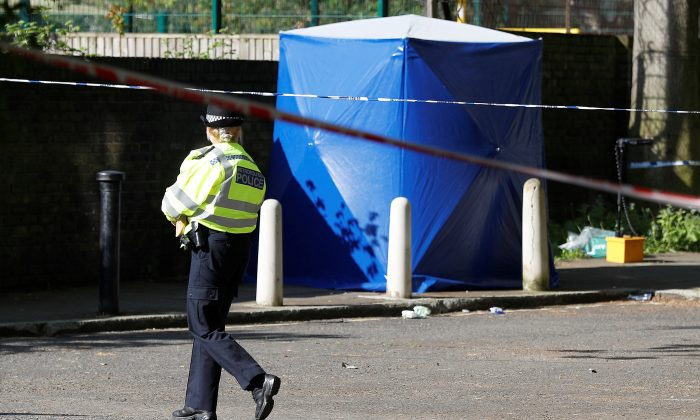 A police officer walks inside a cordon at the scene where a teenager was found after being shot, on Saturday, in London, Britain May 6, 2018. (Reuters/Peter Nicholls)